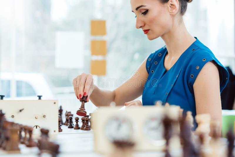 Kvinna som spelar schack i turnering royaltyfri foto