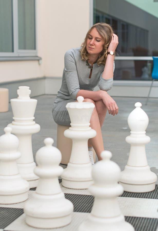 Kvinna som spelar schackleken arkivbilder