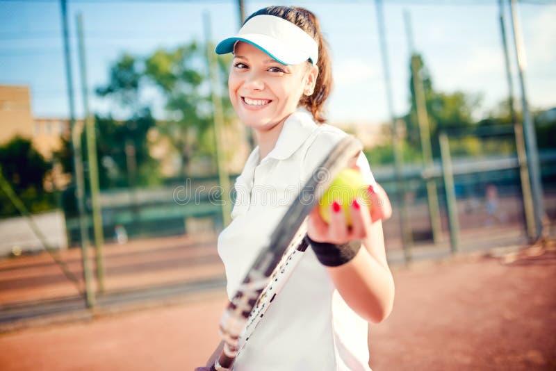Kvinna som spelar tennis, hållande racket och bollen T-skjorta och lock för attraktiv brunettflicka bärande vit på tennisbanan fotografering för bildbyråer