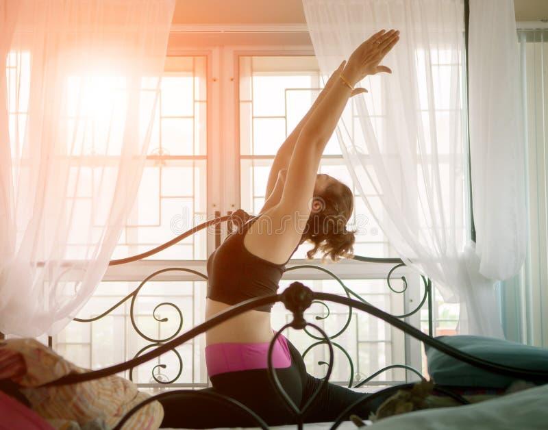 Kvinna som spelar yoga för hälsa i hem- sängrum arkivbilder