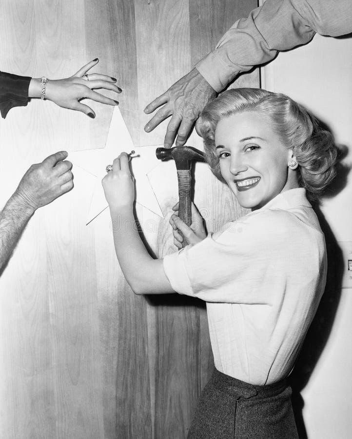 Kvinna som spikar upp stjärnan med portionhänder (alla visade personer inte är längre uppehälle, och inget gods finns Leverantörg royaltyfria foton
