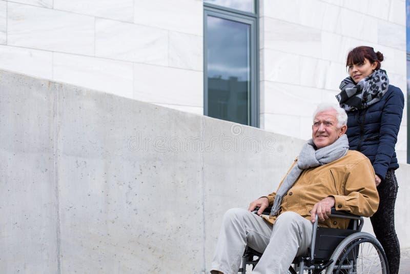 Kvinna som stöttar henne rörelsehindrad fader arkivbild