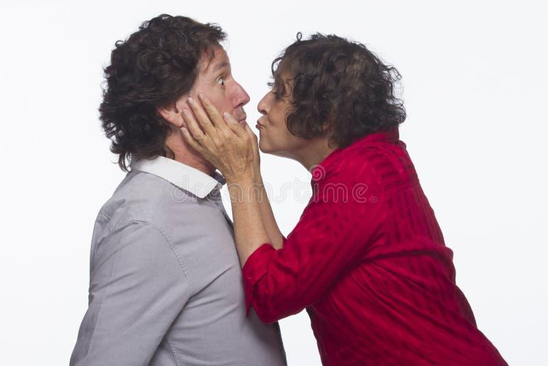Kvinna som stjäler en kyss från mannen som är horisontal royaltyfri bild