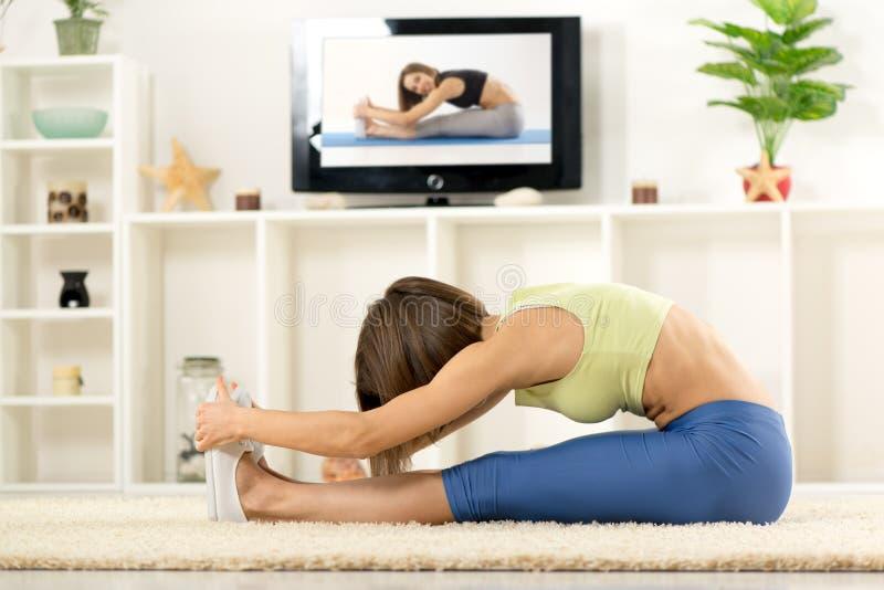 Kvinna som sträcker i Front Of TV arkivbild