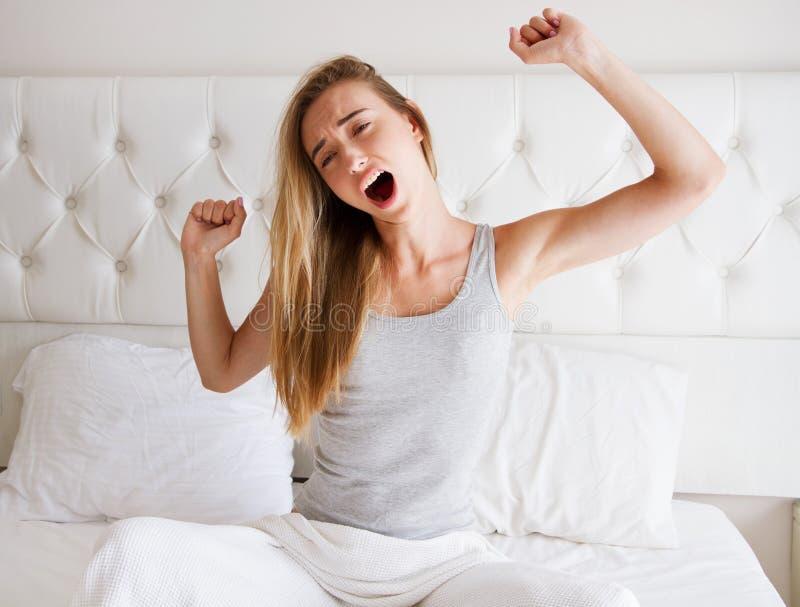 Kvinna som sträcker i säng efter vak upp, främre sikt fotografering för bildbyråer
