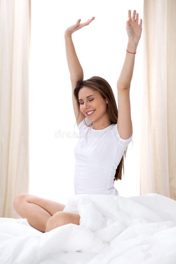 Kvinna som sträcker i säng efter vak upp och att skriva in en avkopplad dag som är lycklig och efter sömn för bra natt Söta drömm arkivbilder