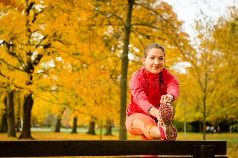Kvinna som sträcker, innan att jogga royaltyfri bild