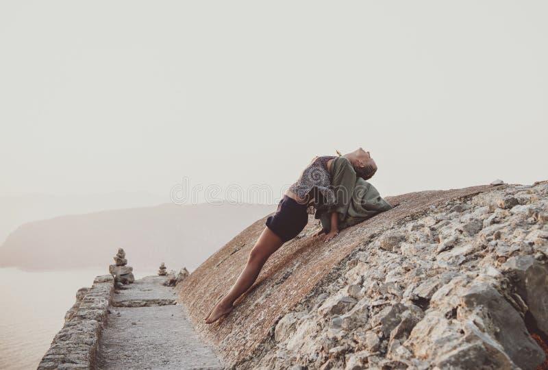 Kvinna som sträcker kroppen på stenar i Monolithos, Rhodes, Grekland arkivbild