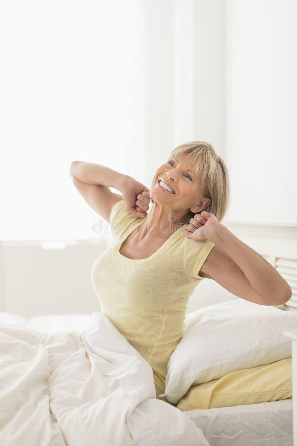 Kvinna som sträcker, medan sitta i säng royaltyfria bilder