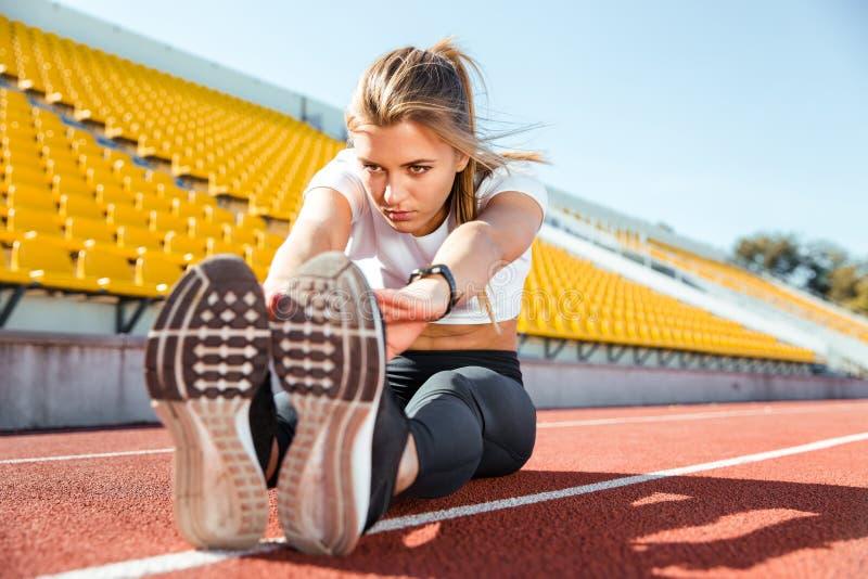 Kvinna som sträcker på golvet på stadion arkivbilder