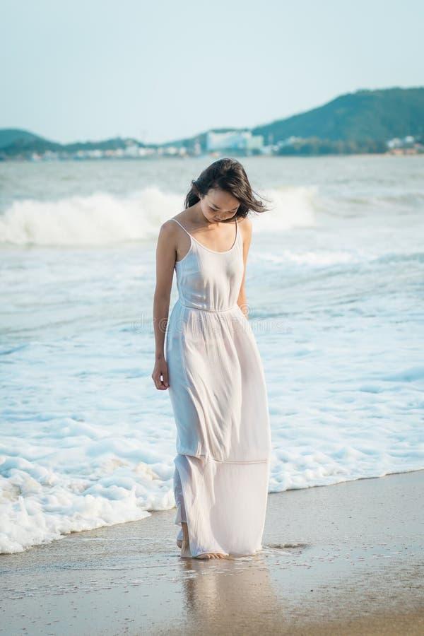 Kvinna som strosar på stranden i sommar Lycklig blandras- asiatisk flicka som går till havet royaltyfri foto