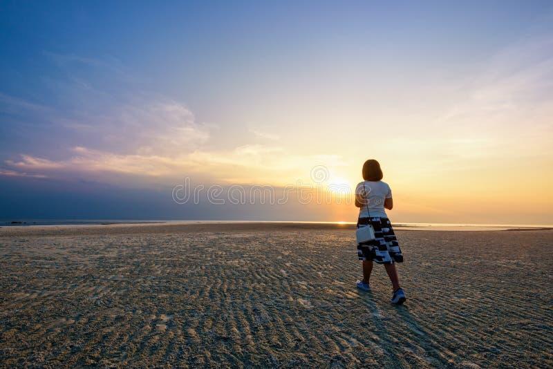Kvinna som strosar på stranden på solnedgången royaltyfria bilder