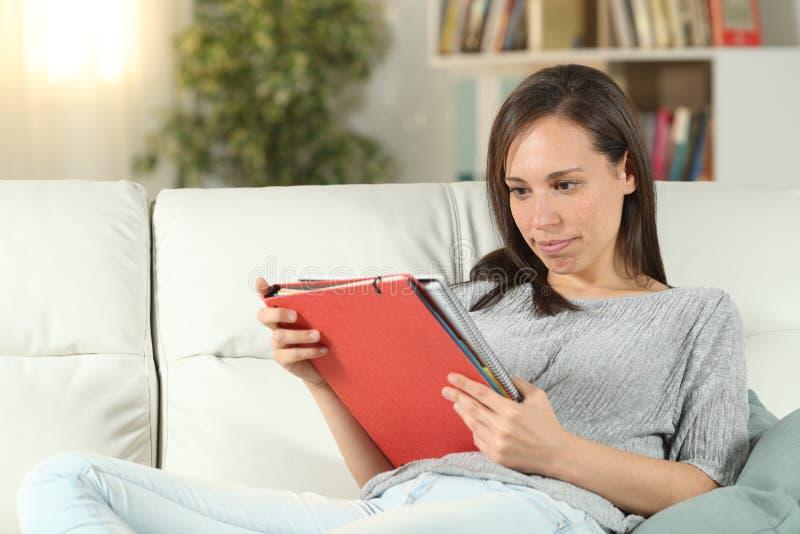 Kvinna som studerar läsninganmärkningar som sitter på en soffa royaltyfri fotografi