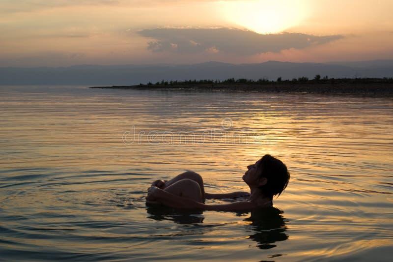 Kvinna som svävar i det döda havet på solnedgången arkivbild