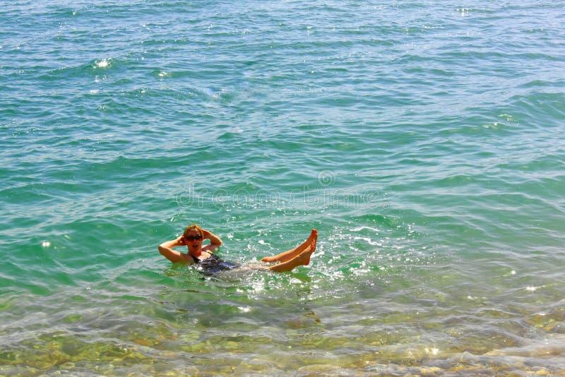 Kvinna som svävar i det döda havet som kopplas av på ferie royaltyfri fotografi