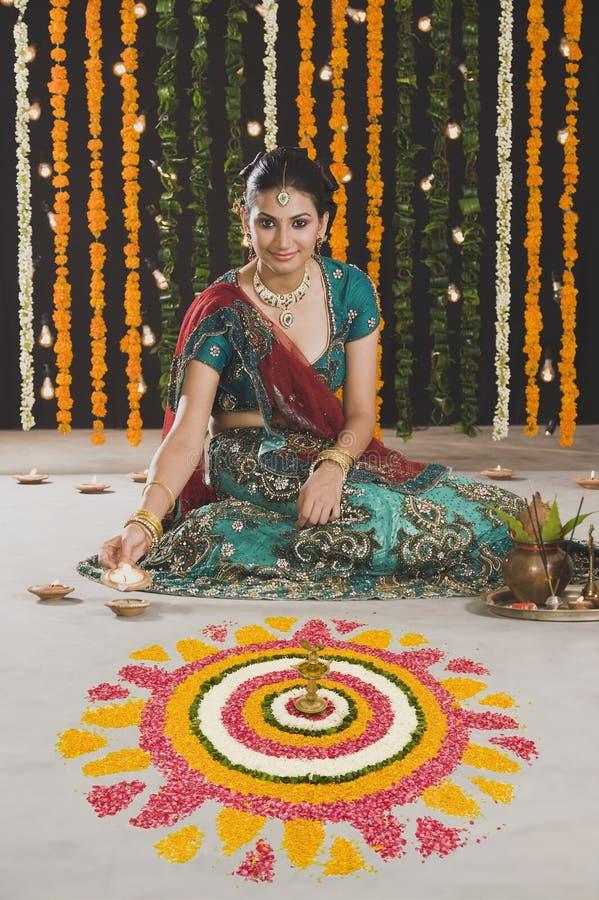 Kvinna som tänder olje- lampor på Diwali royaltyfri fotografi