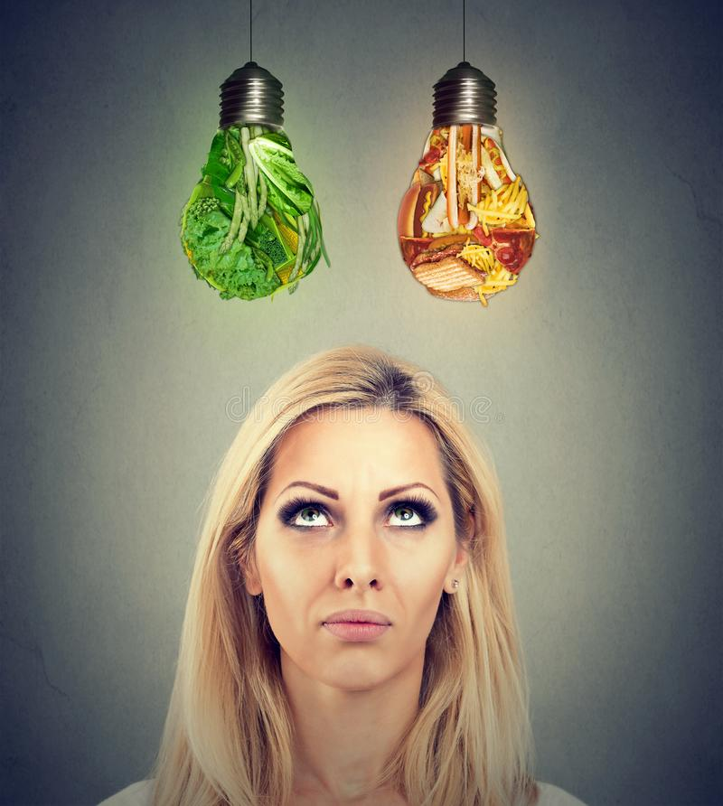 Kvinna som tänker göra ett bantaval som ser upp på skräpmat- och gräsplangrönsaker som formas som ljus kula royaltyfria foton