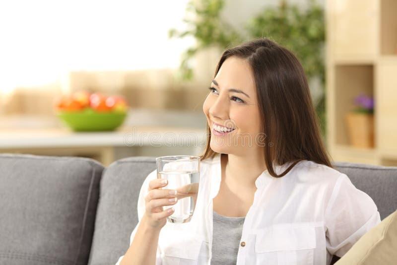 Kvinna som tänker och rymmer ett exponeringsglas av vatten arkivfoto