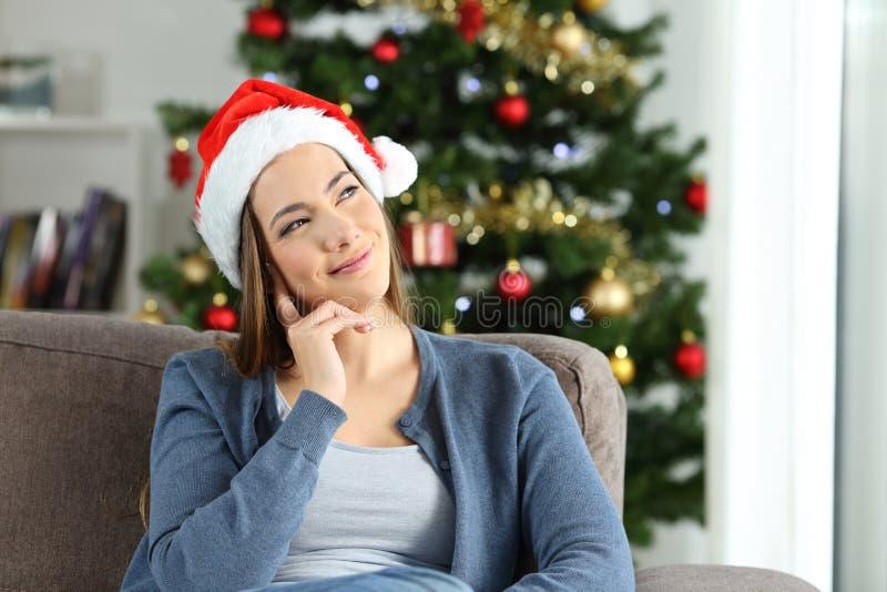 Kvinna som tänker se sidan hemma i jul fotografering för bildbyråer
