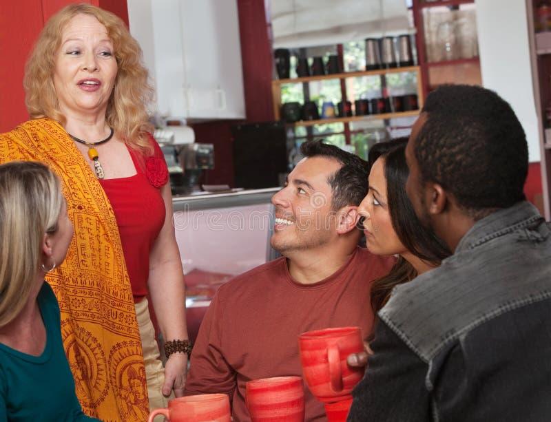 Kvinna som talar med vänner i Cafe royaltyfri bild