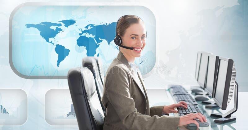 Kvinna som talar på hörlurar med mikrofon och använder datoren i call center med världskartan i bakgrund arkivfoto