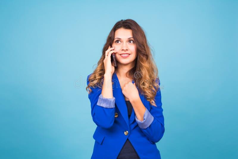 Kvinna som talar på hennes mobiltelefon över en blå bakgrund fotografering för bildbyråer