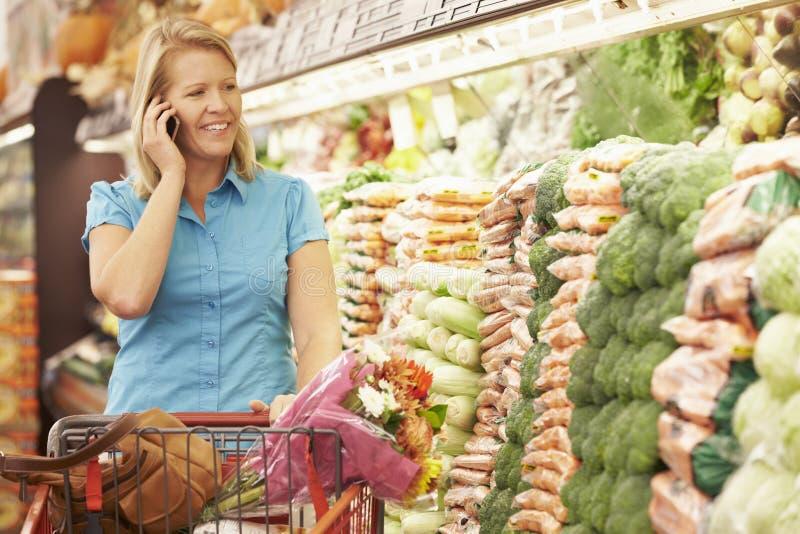 Kvinna som talar på mobiltelefonen i supermarket fotografering för bildbyråer