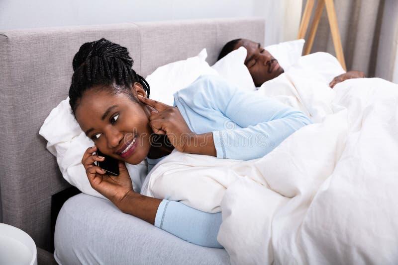 Kvinna som talar p? mobiltelefonen medan hennes make som sover p? s?ng fotografering för bildbyråer