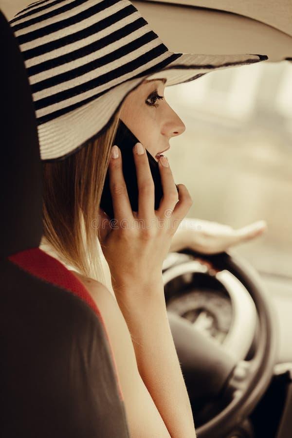 Kvinna som talar på mobiltelefonen, medan köra hennes bil royaltyfri foto