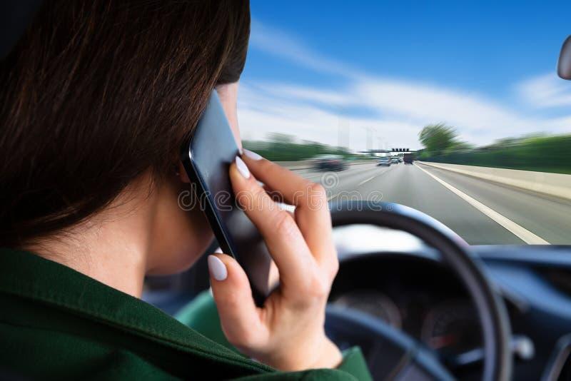 Kvinna som talar p? mobiltelefonen, medan rida bilen royaltyfria bilder