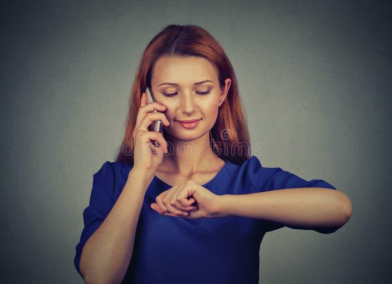 Kvinna som talar på mobiltelefonen som ser armbandsuret arkivbilder