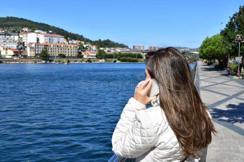 Kvinna som talar på telefonen i en promenad med träd Blå flod, vit kläder, vit smarphone Ingen märke eller logo solig dag arkivbild