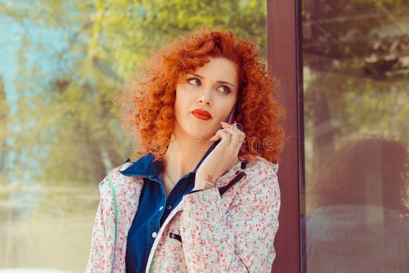 Kvinna som talar på telefonen, medan sitta i en bussstation utanför in arkivfoto