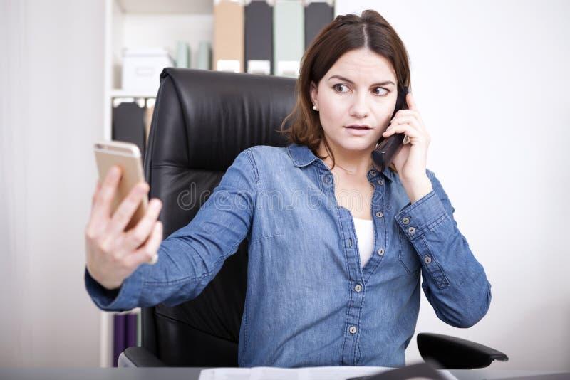 Kvinna som talar på telefonen och kontrollerar hennes mobil royaltyfria foton