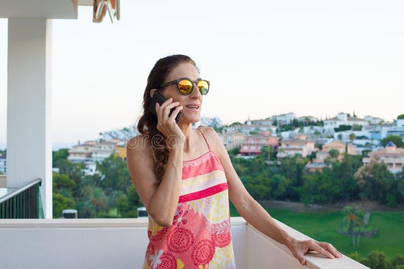 Kvinna som talar på telefonen på terrassen arkivbild