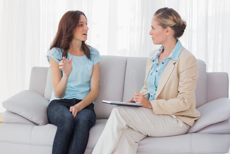 Kvinna som talar till hennes psykolog royaltyfri foto