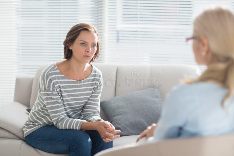 Kvinna som talar till hennes terapeut arkivbild