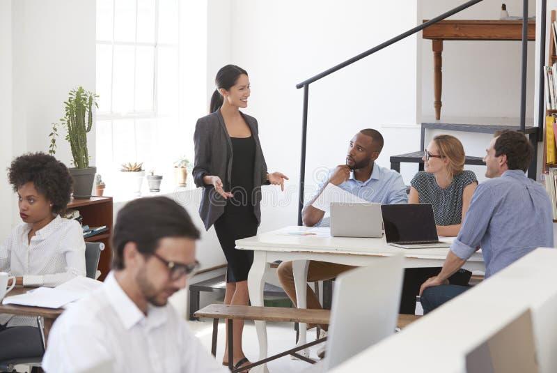 Kvinna som talar till kollegor på ett skrivbord i öppet plankontor royaltyfria bilder