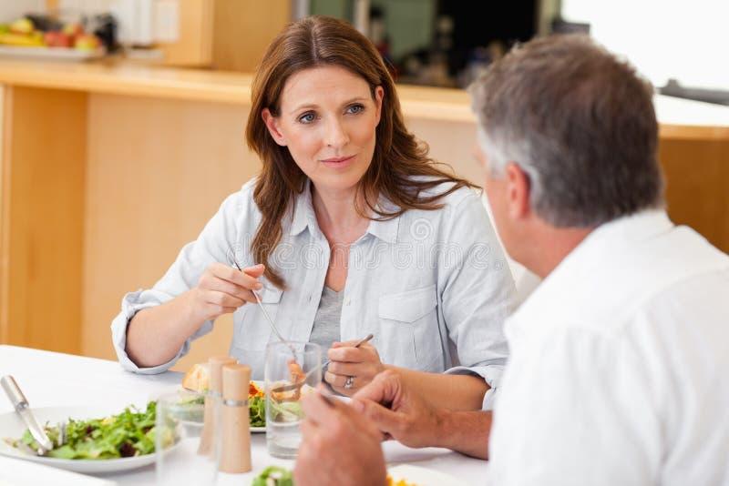 Kvinna som talar till makan under matställe royaltyfri fotografi