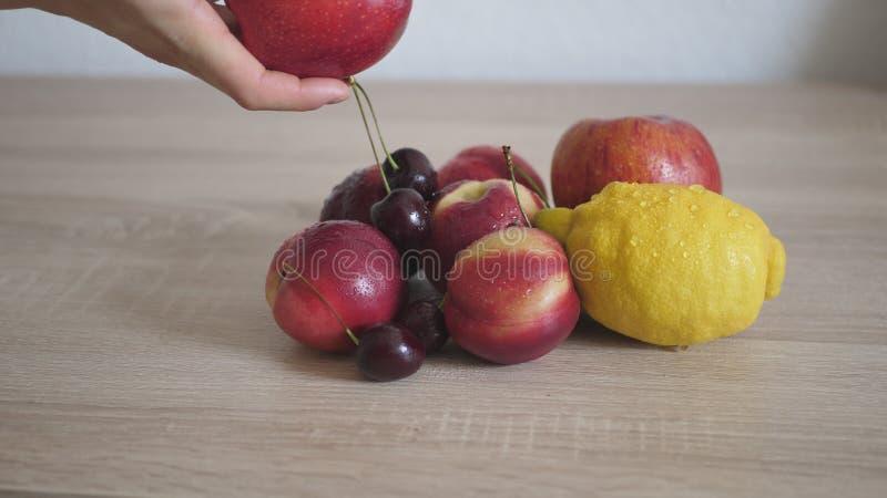 Kvinna som tar äpplet från trätabellen royaltyfri foto