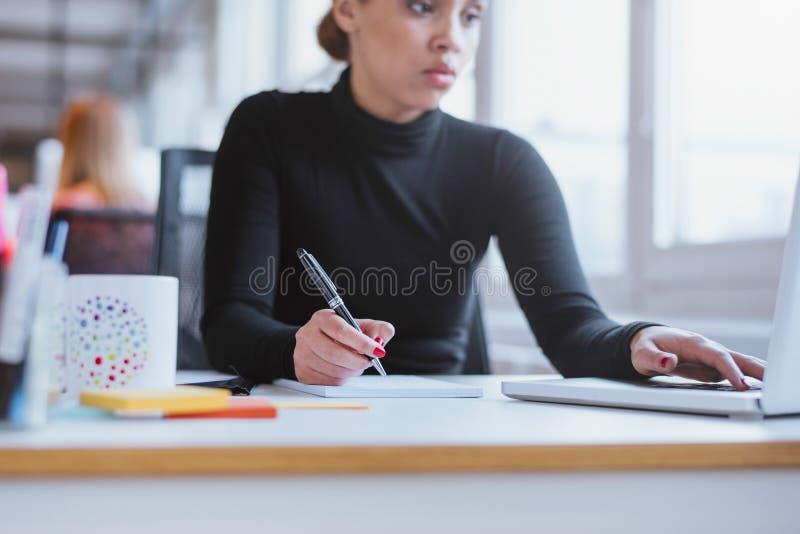 Kvinna som tar anmärkningar från bärbara datorn arkivbild