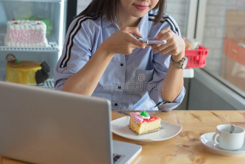 Kvinna som tar bilden av strawberykakan med smartphonen arkivbild