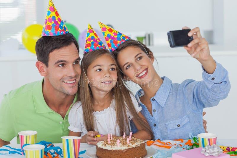 Kvinna som tar bilder av hennes familj under ett födelsedagparti royaltyfria foton