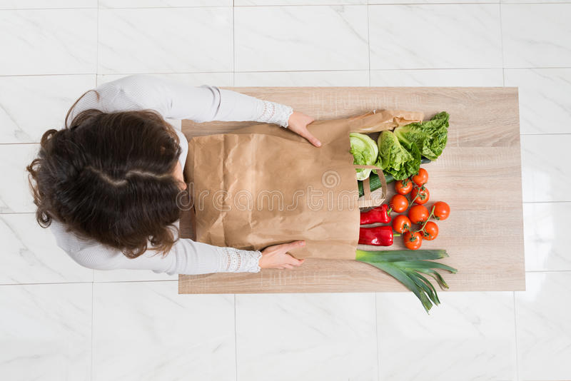 Kvinna som tar bort grönsaker från shoppingpåse royaltyfria bilder