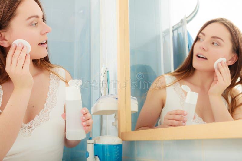 Kvinna som tar bort makeup med blocket för bomullsbomullstopp royaltyfri bild