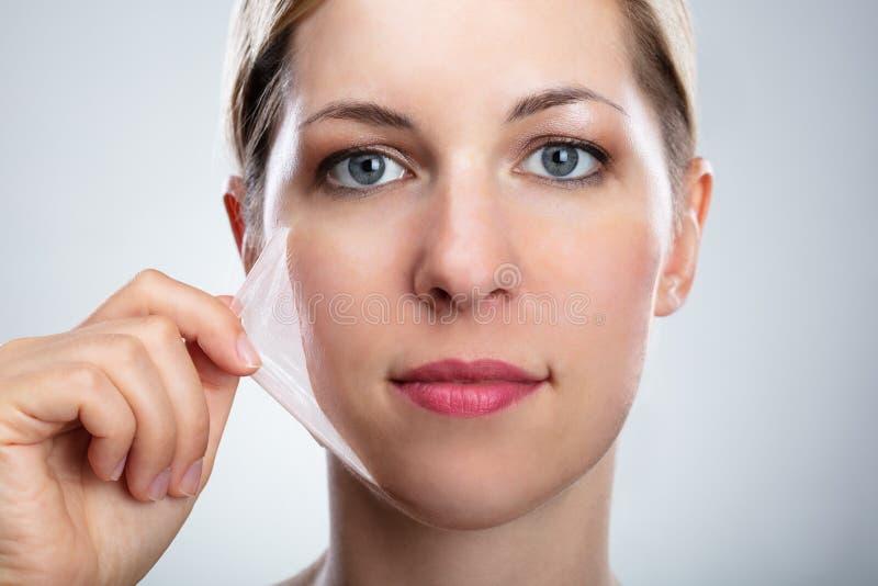 Kvinna som tar bort skala maskeringen fr?n hennes framsida royaltyfria foton