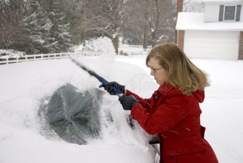 Kvinna som tar bort Snow från bil 5 royaltyfri foto