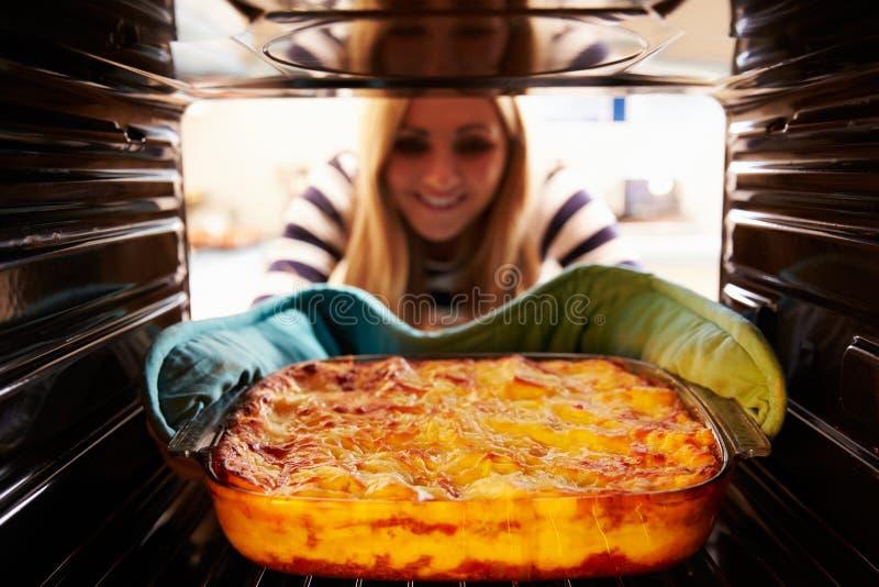 Kvinna som tar den lagade mat maträtten av lasagnen ut ur ugnen arkivbild