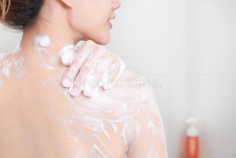 Kvinna som tar en dusch som tycker om med skumbadet arkivfoto