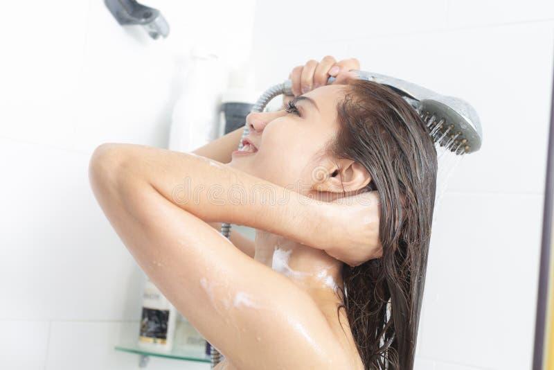 Kvinna som tar en dusch som tycker om vatten som plaskar p? henne arkivfoto